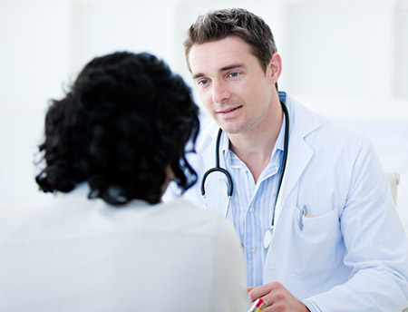 Handsome doctor talking with his patient for the annual check-up in the hospital; Shutterstock ID 52821718; PO: 159025.5